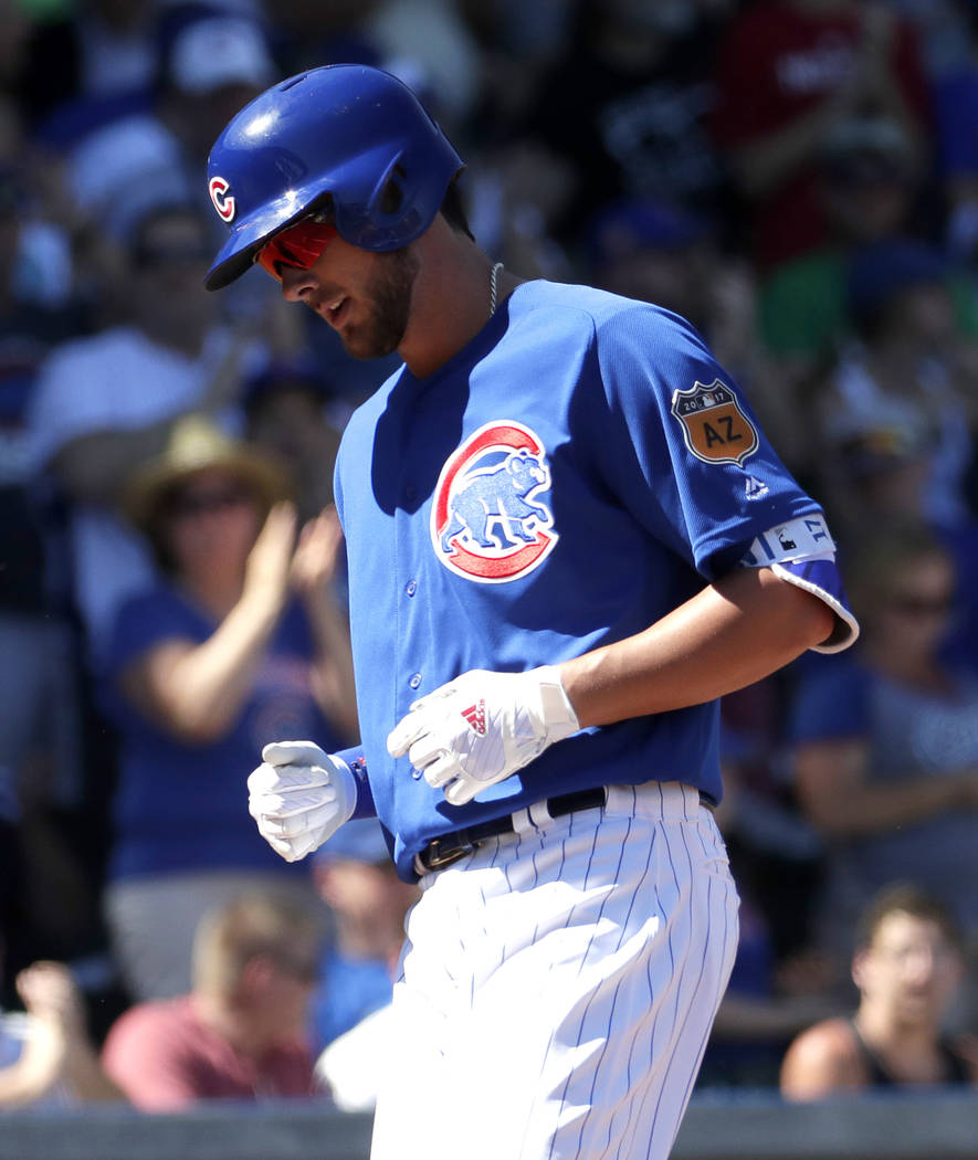 Chicago Cubs' Kris Bryant scores after hitting a solo home run against the Milwaukee Brewers during the first inning of a spring training baseball game, Tuesday, March 14, 2017, in Mesa, Ariz. (AP ...