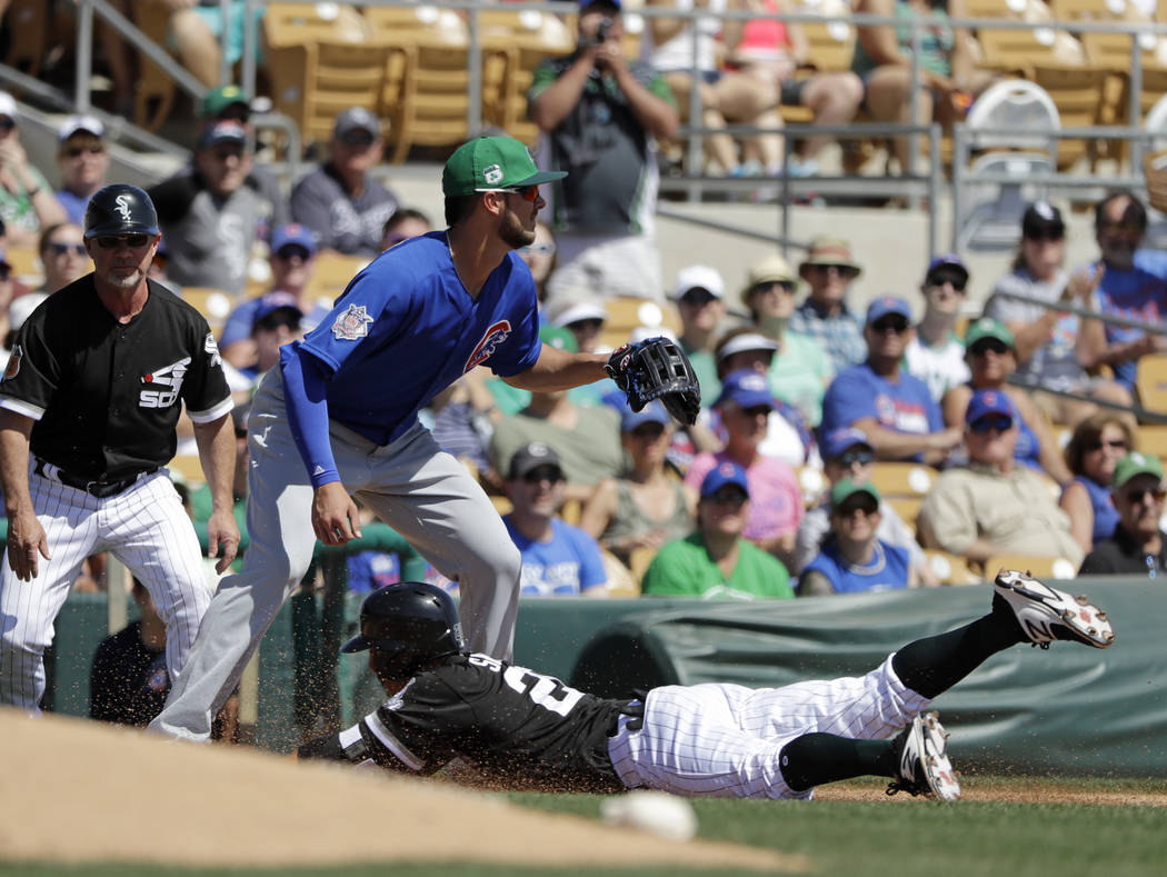 Chicago White Sox's Tyler Saladino slides safe into third as Chicago Cubs' Kris Bryant takes the throw during the second inning of a spring training baseball game Friday, March 17, 2017, in Phoeni ...