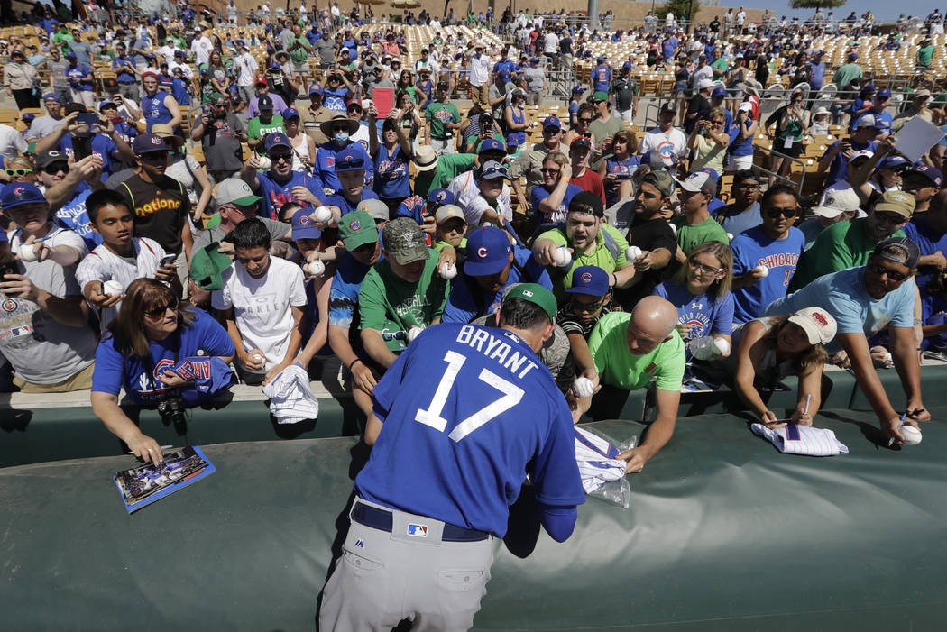 Chicago Cubs' Kris Bryant signs autographs during a spring training baseball game against the Chicago White Sox, Friday, March 17, 2017, in Phoenix. (AP Photo/Darron Cummings)