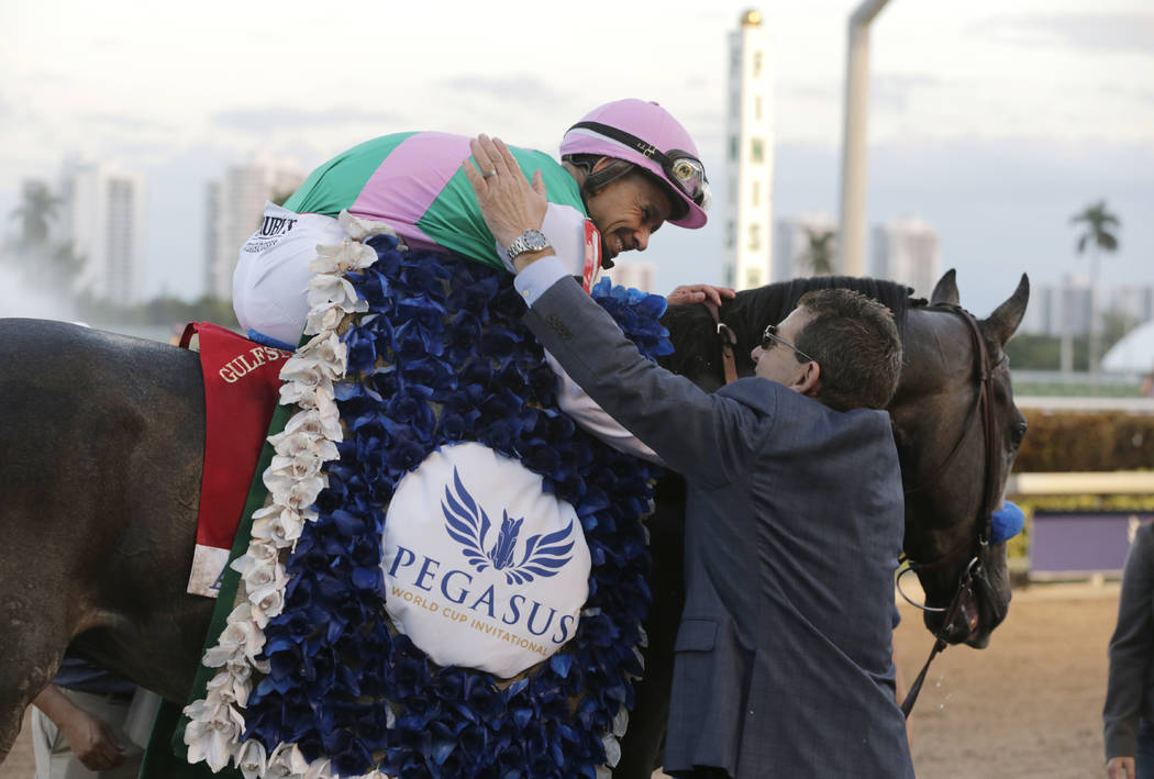 Jockey Mike Smith is congratulated by assistant trainer Jim Barnes after riding Arrogate to victory in the inaugural running of the $12 million Pegasus World Cup horse race at Gulfstream Park, Sat ...