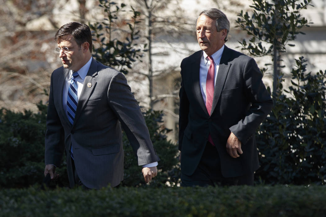 Members of the House Freedom Caucus Rep. Justin Amash, R-Mich., left, and Rep. Mark Sanford, R-S.C., arrive at the White House in Washington, Thursday, March 23, 2017. (AP Photo/Evan Vucci)