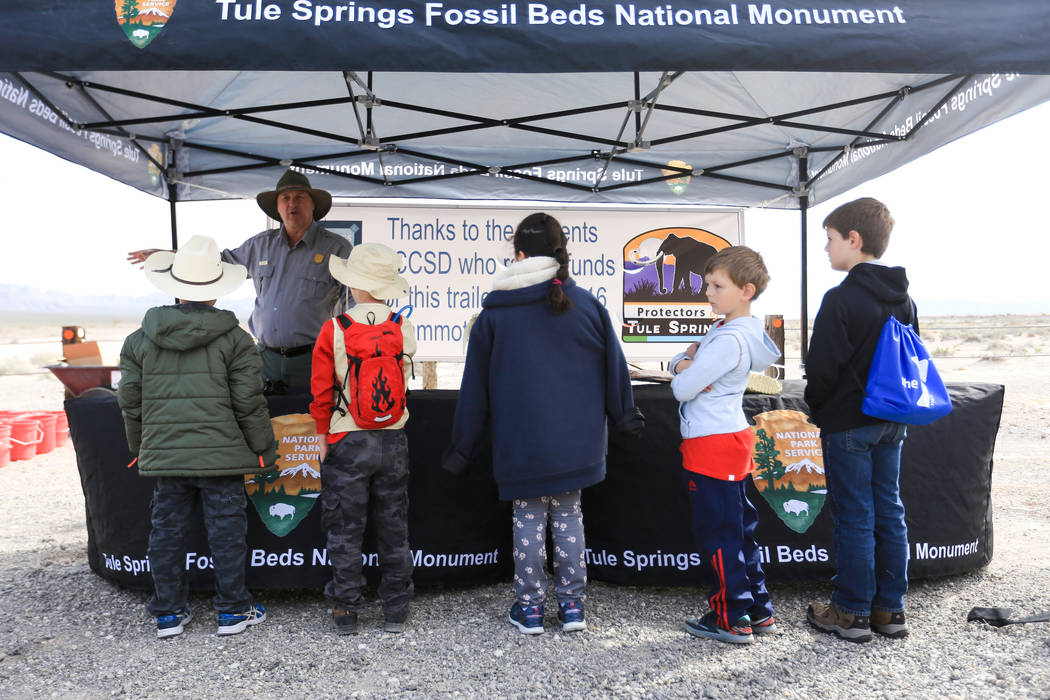 National Park Service worker Curt Barbach shows replica fossils to a group of kids that will help clean trash at Tule Springs Fossil Beds National Monument in Las Vegas on Saturday, March 4, 2017, ...