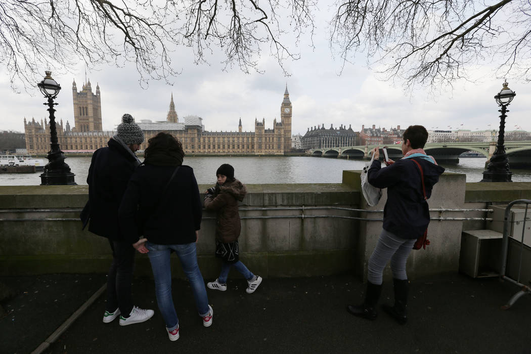 Tourists view parliament from across the River Thames, with Westminster Bridge, right, in London, Thursday March 23, 2017, the scene of an attack. (Tim Ireland/AP)