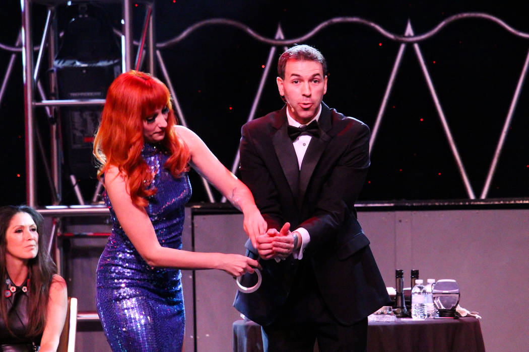 "Stage assistant Kady Heard snaps the handcuffs on Jason Hanson in ""Spy Escape & Evasion"" at the Stratosphere. (Courtesy)"