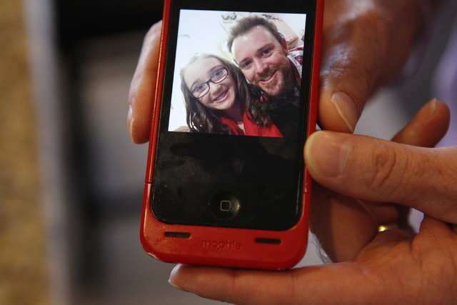 Jason Lamberth shows a picture with his daughter in his phone during an interview at his home in Henderson Tuesday, Oct. 21, 2014. His 13-year-old daughter, Hailee, was being bullied at school bef ...