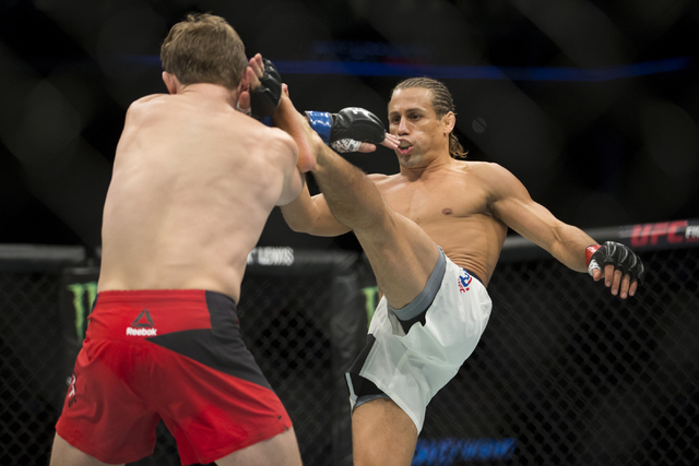 Urijah Faber, right, kicks Brad Pickett in the UFC Fight Night bantamweight bout at the Golden 1 Center on Saturday, Dec. 17, 2016, in Sacramento, Calif. Faber won by unanimous decision. (Erik Ver ...