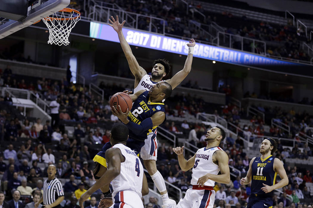 West Virginia guard Jevon Carter (2) drives to the basket as Gonzaga guard Josh Perkins, top, defends during the first half of an NCAA Tournament college basketball regional semifinal game Thursda ...