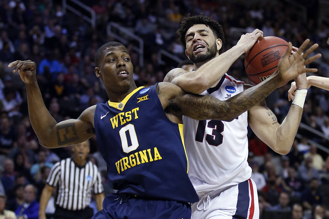 Gonzaga guard Josh Perkins (13) grabs a rebound next to West Virginia guard Teyvon Myers during the second half of an NCAA Tournament college basketball regional semifinal game Thursday, March 23, ...