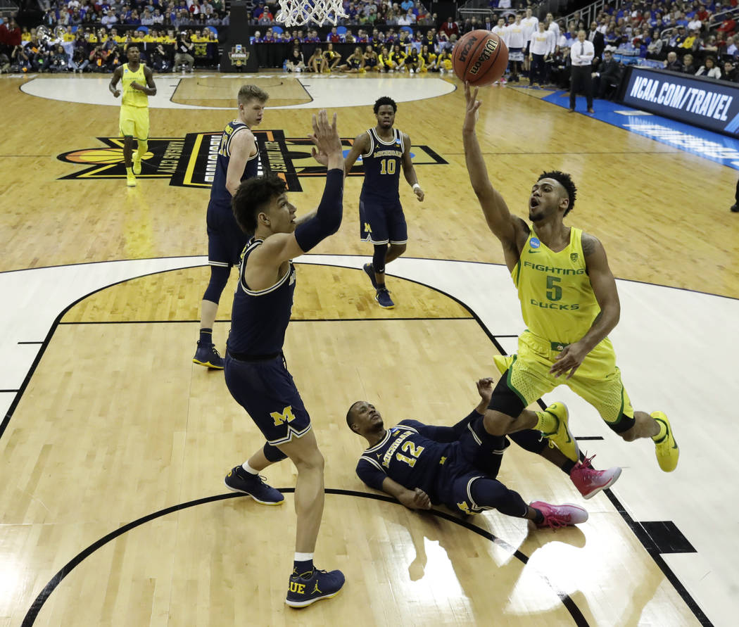 Oregon guard Tyler Dorsey (5) drives to the basket over Michigan's D.J. Wilson, left, and Muhammad-Ali Abdur-Rahkman (12) during the second half of a regional semifinal of the NCAA men's college b ...