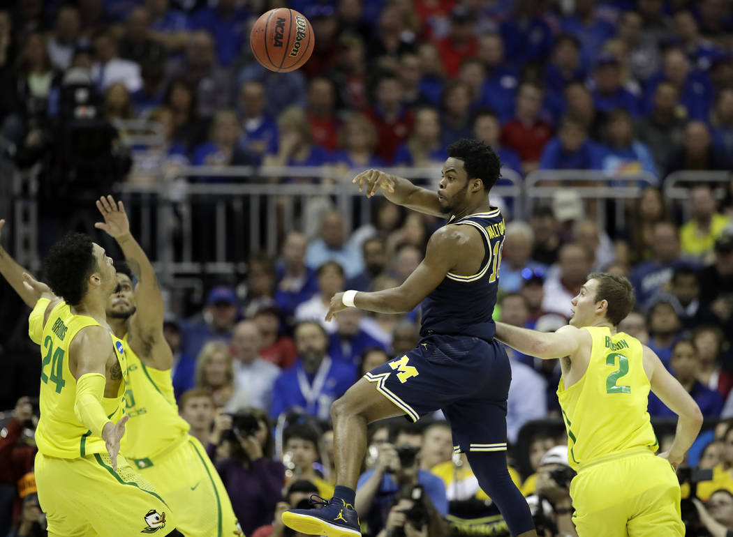 Michigan guard Derrick Walton Jr., center, passes between Oregon's Dillon Brooks, left, and Casey Benson, right, during the second half of a regional semifinal of the NCAA men's college basketball ...
