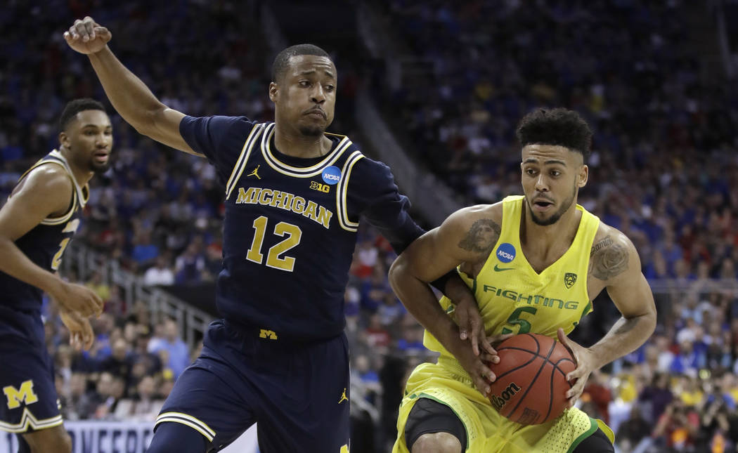Oregon guard Tyler Dorsey drives past Michigan guard Muhammad-Ali Abdur-Rahkman (12) during the second half of a regional semifinal of the NCAA men's college basketball tournament, Thursday, March ...