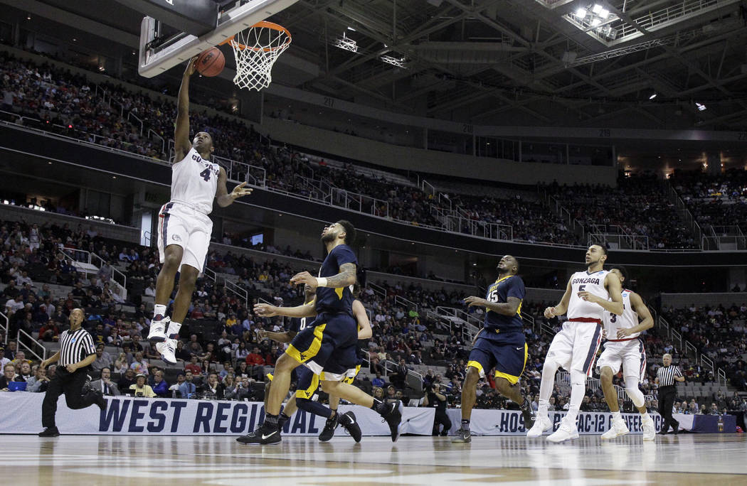 Gonzaga guard Jordan Mathews, top left, drives to the basket against West Virginia during the first half of an NCAA Tournament college basketball regional semifinal game Thursday, March 23, 2017,  ...