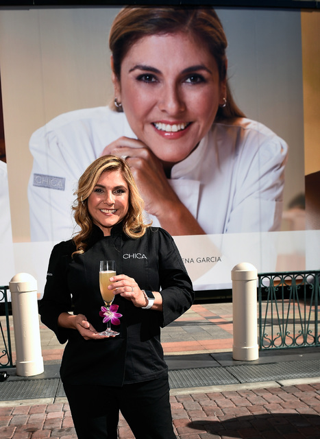 Chef Lorena Garcia stands by a 21-foot-tall poster of herself after its debut on the wall of chefs at The Venetian on Wednesday, Feb. 15, 2017, in Las Vegas. Garcia, who will be opening her first  ...