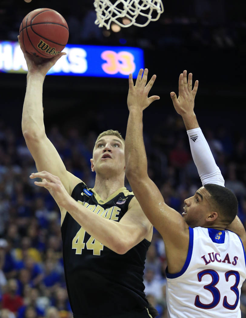 Purdue center Isaac Haas shoots next to Kansas forward Landen Lucas during the first half of a regional semifinal of the NCAA men's college basketball tournament, Thursday, March 23, 2017, in Kans ...