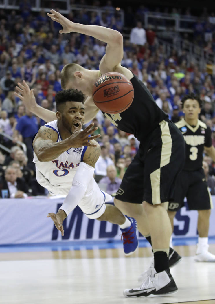 Kansas guard Frank Mason III passes around Purdue center Isaac Haas during the first half of a regional semifinal of the NCAA men's college basketball tournament, Thursday, March 23, 2017, in Kans ...