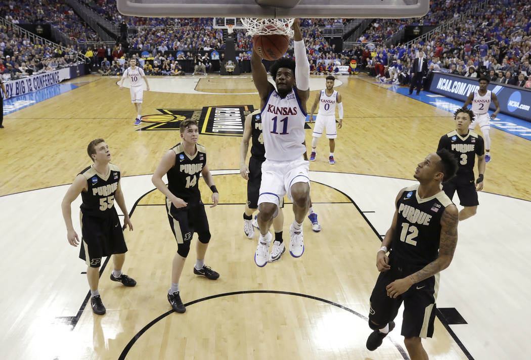 Kansas guard Josh Jackson (11) dunks over Purdue's Spike Albrecht (55), Ryan Cline (14) and Vince Edwards, right, during the first half of a regional semifinal of the NCAA men's college basketball ...