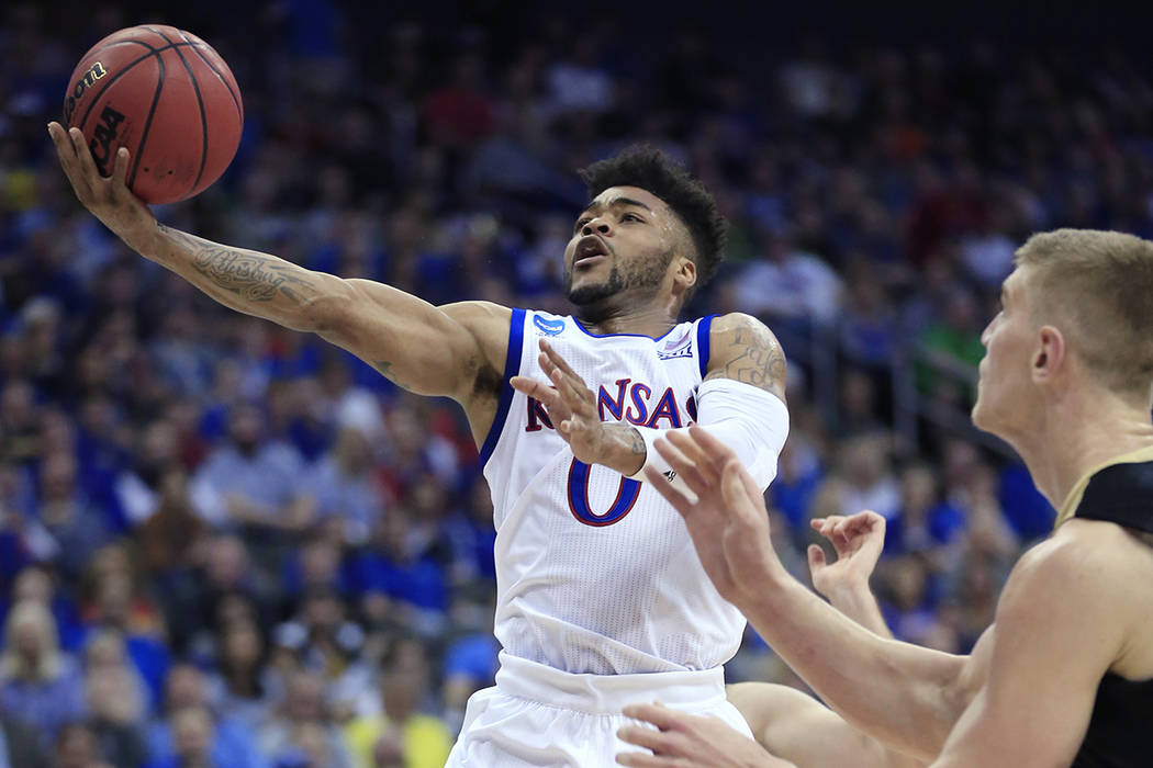 Kansas guard Frank Mason III drives to the basket next to Purdue center Isaac Haas during the second half of a regional semifinal of the NCAA men's college basketball tournament, Thursday, March 2 ...