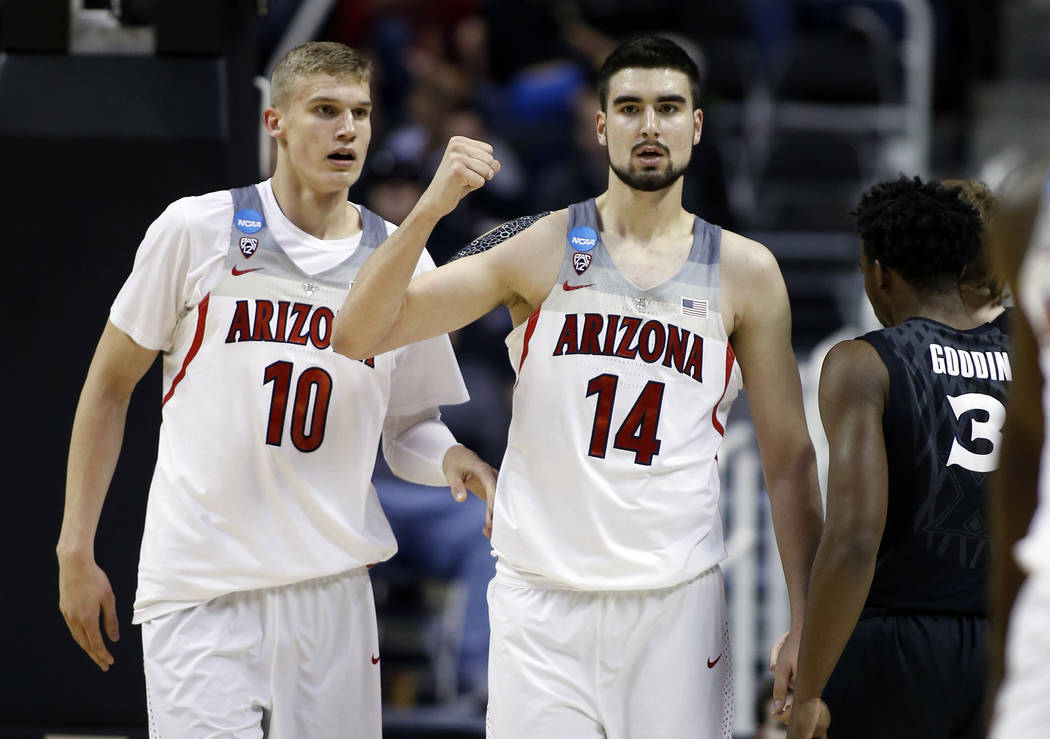Arizona center Dusan Ristic (14) celebrates after scoring with teammate Lauri Markkanen (10) during an NCAA Tournament college basketball regional semifinal game against against Xavier Thursday, M ...