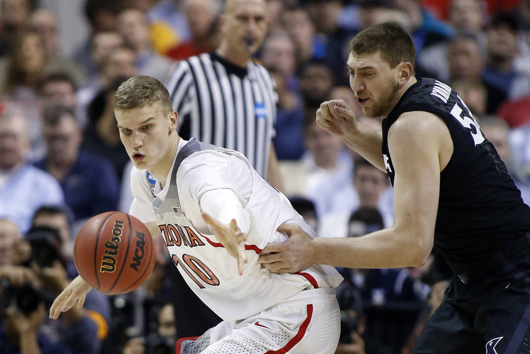 Arizona forward Lauri Markkanen, left, is defended by Xavier's Sean O'Mara during the first half of an NCAA Tournament college basketball regional semifinal game Thursday, March 23, 2017, in San J ...