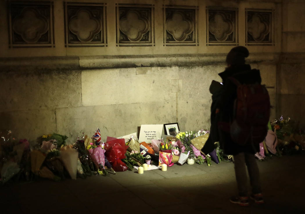 People lay flowers as a tribute to the victims of Wednesday's attack outside the Houses of Parliament, after police cordon was removed in central London, Thursday March 23, 2017.  (Matt Dunham/AP)