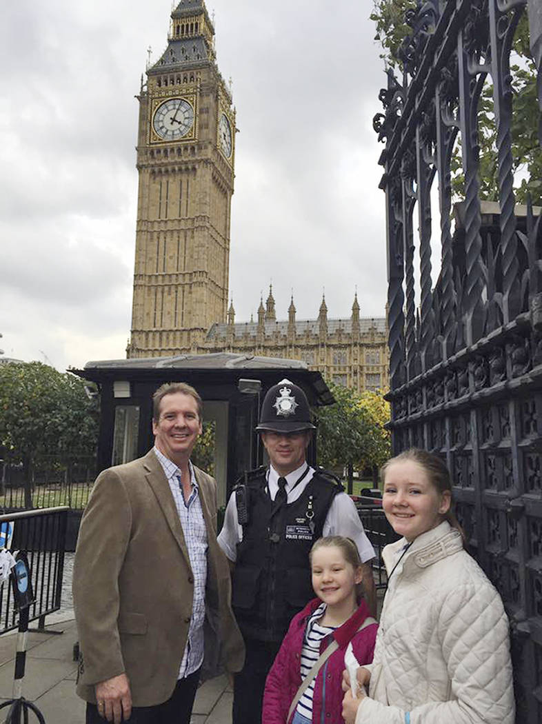In this Oct. 14, 2016, image provided by Claire Thorogood, Andrew Thorogood, left, and his daughters, Alexsandra, second right, and Georgia, right, smile next to Officer Keith Palmer, second left, ...