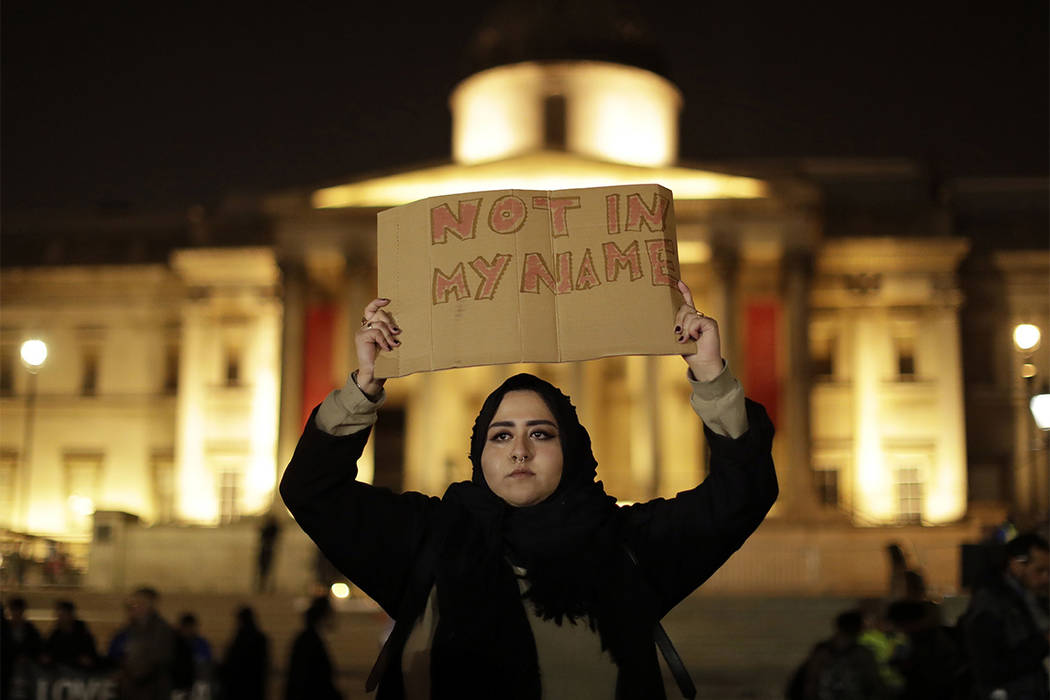 A woman holds up a sign at a vigil for the victims of Wednesday's attack, at Trafalgar Square in London, Thursday, March 23, 2017. (Matt Dunham/AP)