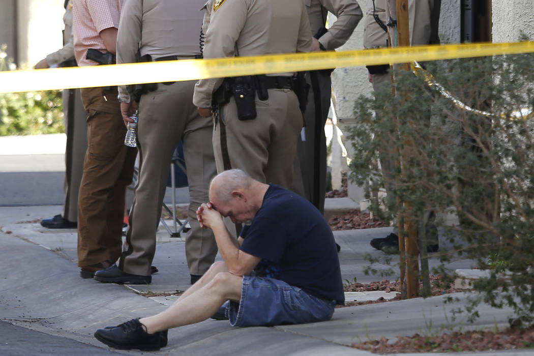 A man sits with his head down where Las Vegas Metropolitan police officers are investigating a shooting near the 10200 block of Yarmouth Sea Ct. on Friday, March 17, 2017, in Las Vegas. (Christian ...