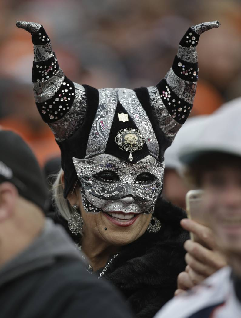 An Oakland Raiders fan wears a mask during an NFL football game against the Denver Broncos, Sunday, Jan. 1, 2017, in Denver. (AP Photo/Joe Mahoney)