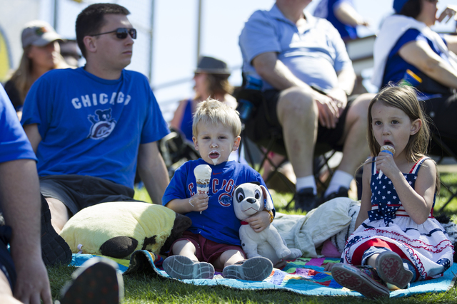 Andy Lenell, from left, and his children David, 2, and Selah, 5, watch the Chicago Cubs play against the New York Mets in their baseball game during Big League Weekend at Cashman Field on Friday,  ...