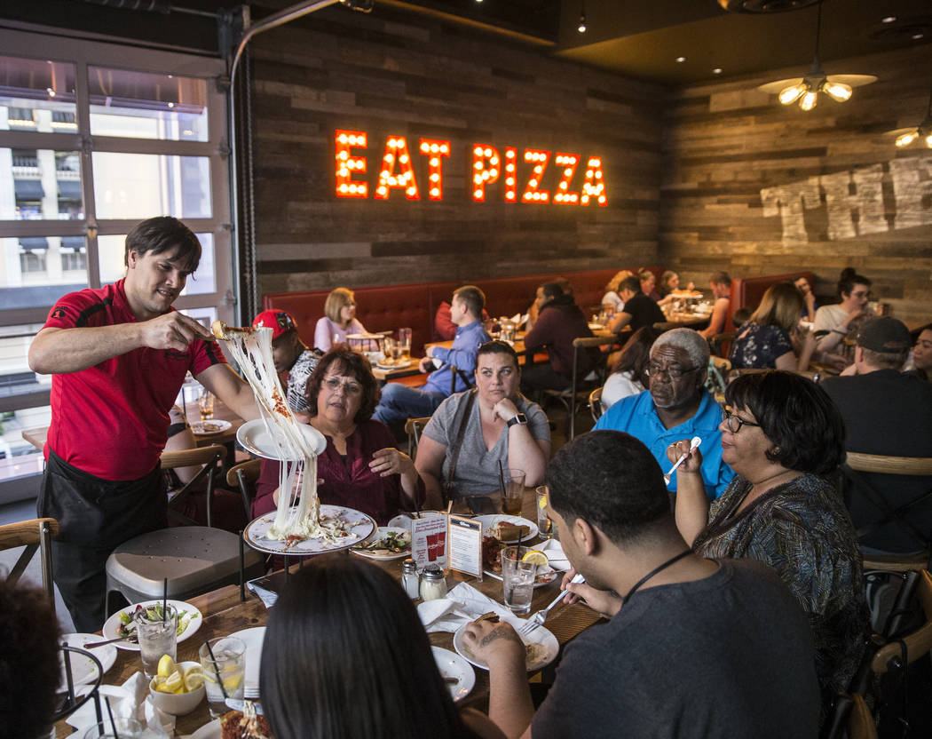 Server Gonzalo Acera, left, plates an extra cheese deep dish pizza at Giordano's on Sunday, March 26, 2017, in Las Vegas. (Benjamin Hager/Las Vegas Review-Journal) @benjaminhphoto
