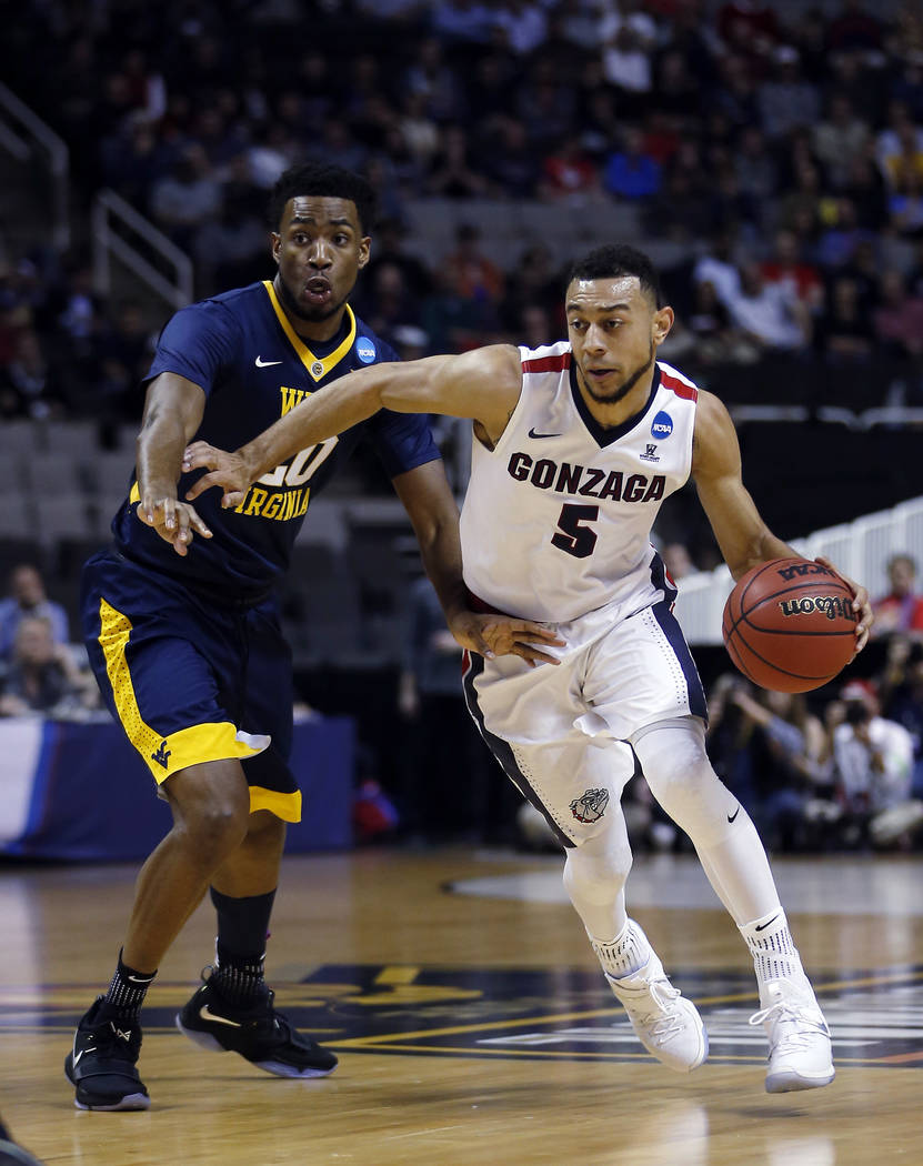 Gonzaga guard Nigel Williams-Goss (5) is defended by West Virginia forward Brandon Watkins during the first half of an NCAA Tournament college basketball regional semifinal game Thursday, March 23 ...
