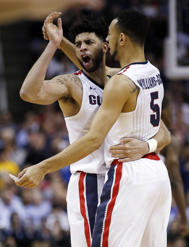 Gonzaga guard Josh Perkins, left, celebrates with teammate Nigel Williams-Goss, right, after a win over West Virginia during the second half of an NCAA Tournament college basketball regional semif ...