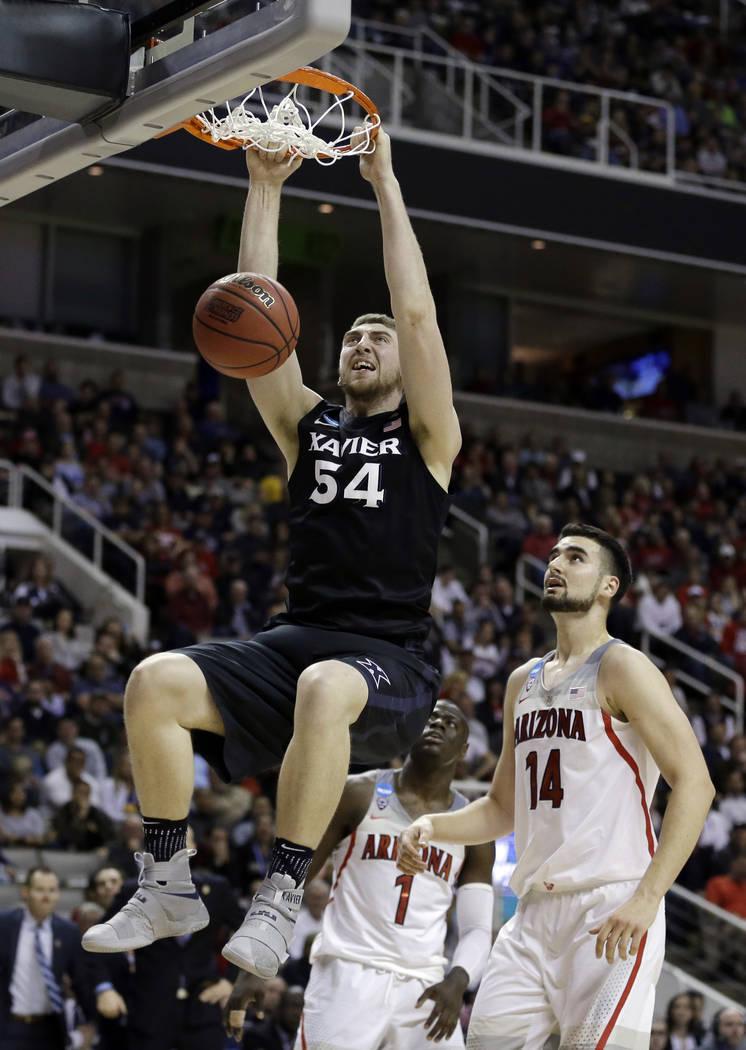 Xavier's Sean O'Mara (54) dunks past Arizona center Dusan Ristic (14) during the second half of an NCAA Tournament college basketball regional semifinal game Thursday, March 23, 2017, in San Jose, ...