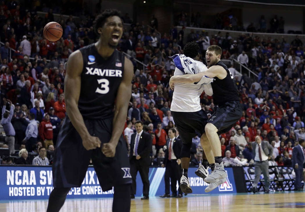 Xavier players including Sean O'Mara, right, and Quentin Goodin (3) celebrate after beating Arizona during an NCAA Tournament college basketball regional semifinal game Thursday, March 23, 2017, i ...