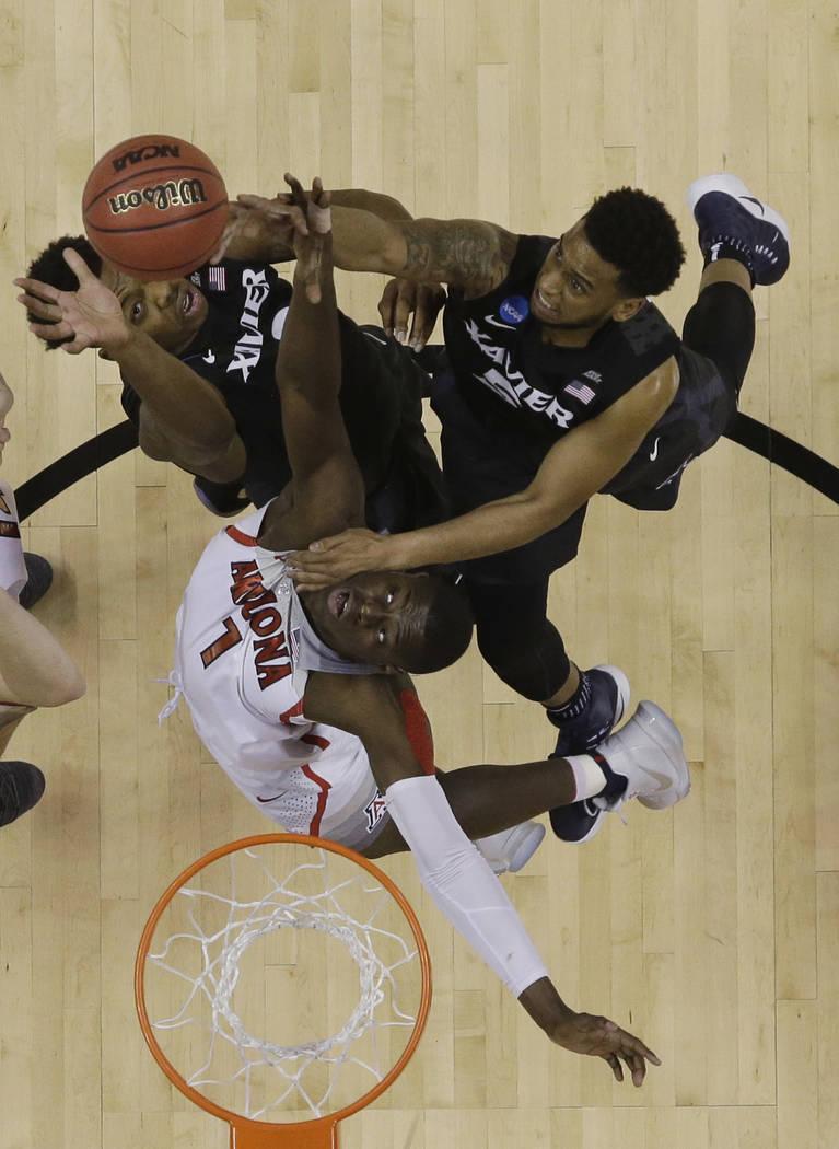 Arizona guard Rawle Alkins (1) vies for a rebound against Xavier guard Trevon Bluiett, top right, and forward Tyrique Jones during an NCAA Tournament college basketball regional semifinal game Thu ...