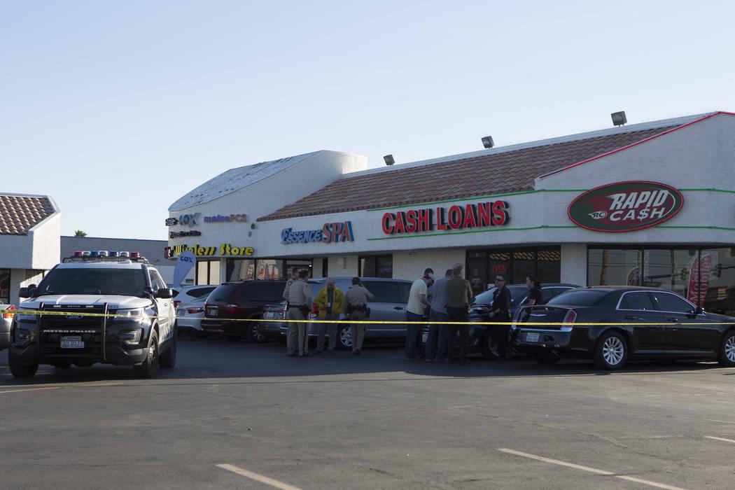 Officers gather in a parking lot outside a Rapid Cash, on W. Flamingo Road near Jones Boulevard, in Las Vegas on Friday, March 24, 2017. (Bridget Bennett/Las Vegas Review-Journal) @bridgetkbennett