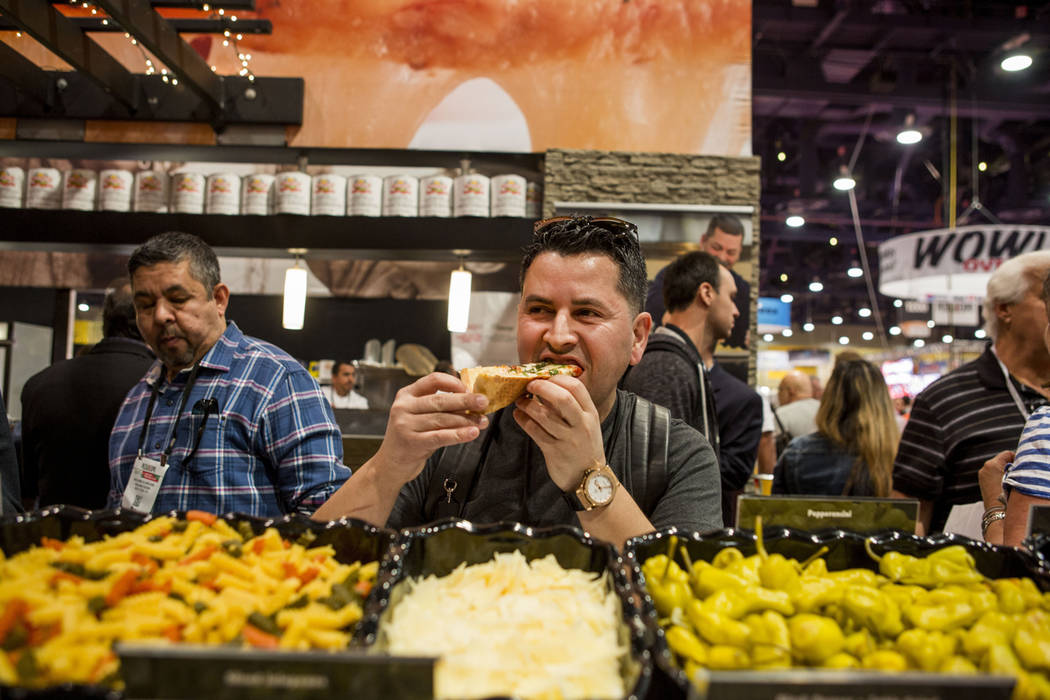 Khalid Elarouss with Poland Foods tastes a slice of Roma Pizza during the International Pizza Expo at the Las Vegas Convention Center in Las Vegas, Tuesday, March 28, 2017. (Elizabeth Brumley/Las  ...