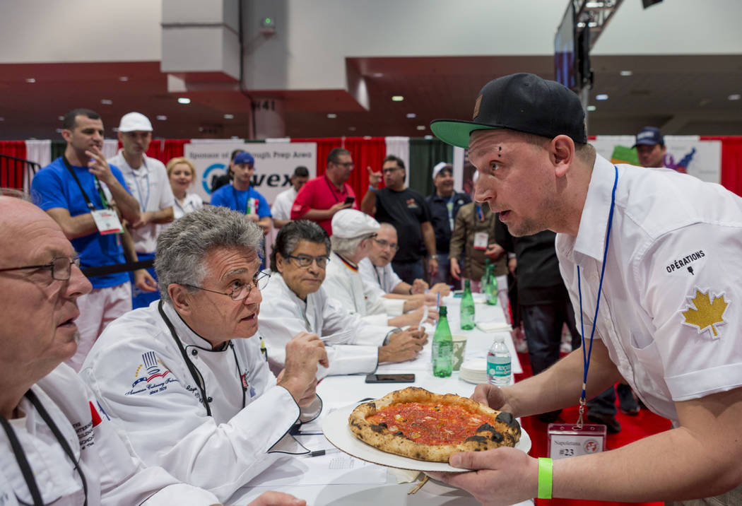 Mirko D' Agata, chef with Pizzria No. 900 Napolitaine, presents his pizza to judges of the International Pizza Competition during the International Pizza Expo at the Las Vegas Convention Center in ...