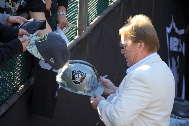 Mark Davis, right, owner and managing general partner of the Oakland Raiders, signs autographs for fans as he walks into the stadium prior to a game at Oakland Colosseum, Sunday, Dec. 4, 2016, in  ...