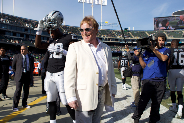 Mark Davis, center, owner and managing general partner of the Oakland Raiders, talks to current and former players and coaches as he walks around the stadium prior to a game at Oakland Colosseum,  ...