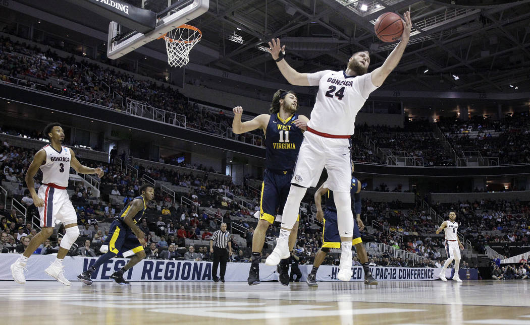 Gonzaga center Przemek Karnowski (24) grabs a rebound next to West Virginia forward Nathan Adrian (11) during the first half of an NCAA Tournament college basketball regional semifinal game Thursd ...
