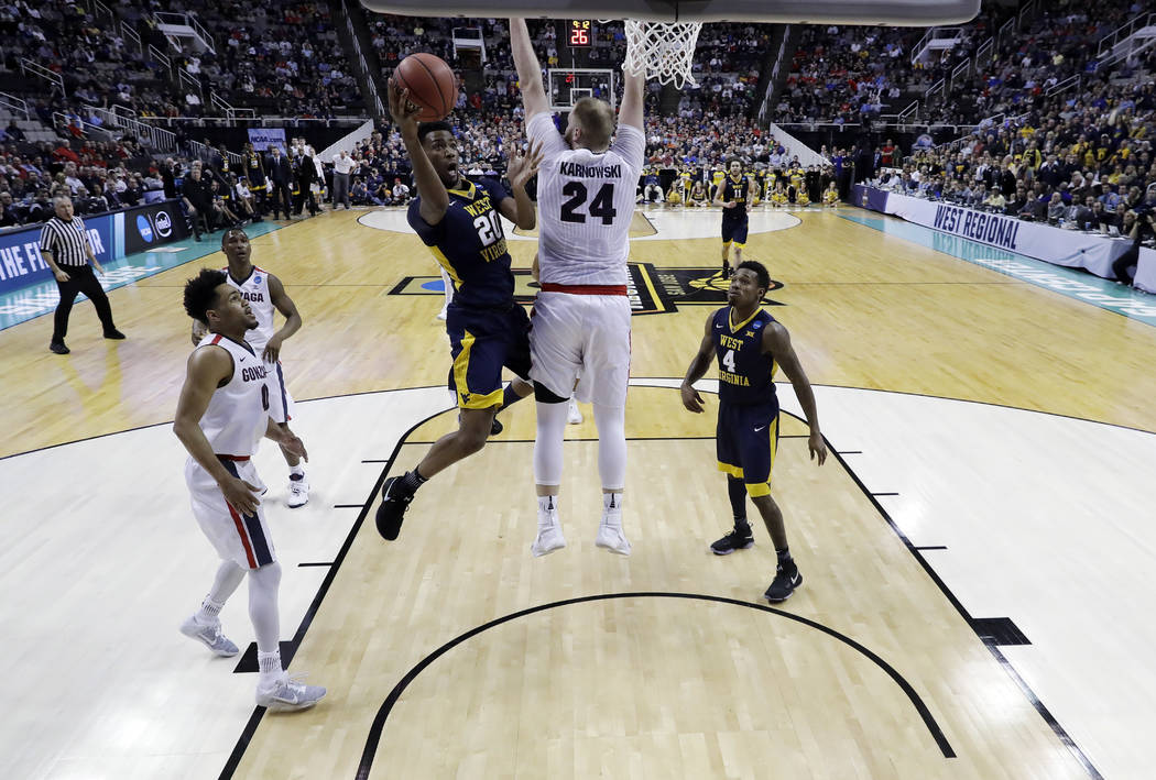 West Virginia forward Brandon Watkins (20) drives to basket as Gonzaga center Przemek Karnowski (24) defends during the first half of an NCAA Tournament college basketball regional semifinal game  ...