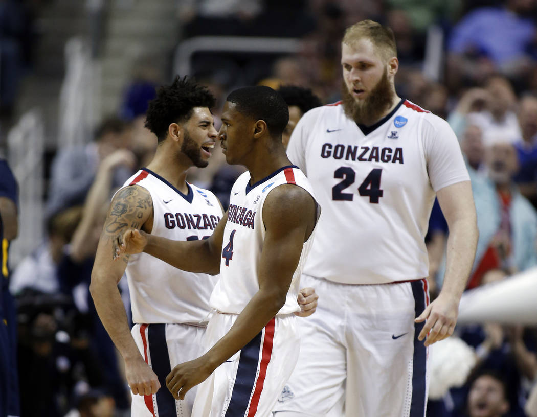 Gonzaga guard Jordan Mathews, center, celebrates after scoring with teammates Josh Perkins, left, and Przemek Karnowski (24) during the second half of an NCAA Tournament college basketball regiona ...