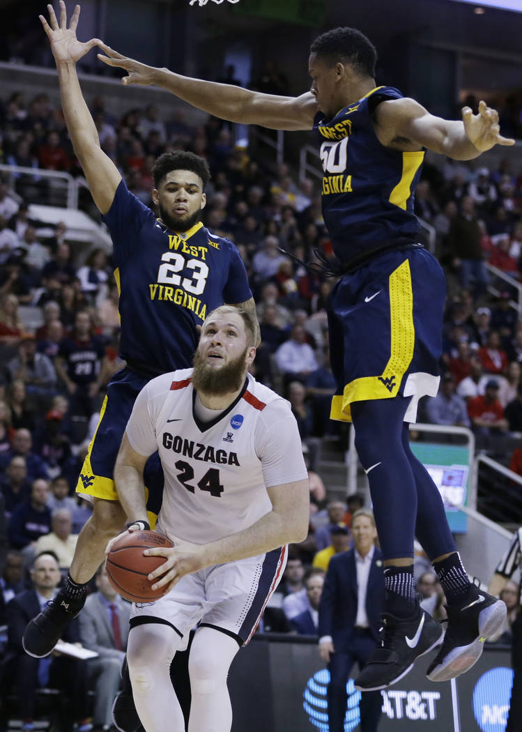 Gonzaga center Przemek Karnowski (24) looks to shoot as West Virginia forward Esa Ahmad (23) and forward Sagaba Konate (50) defend during the second half of an NCAA Tournament college basketball r ...