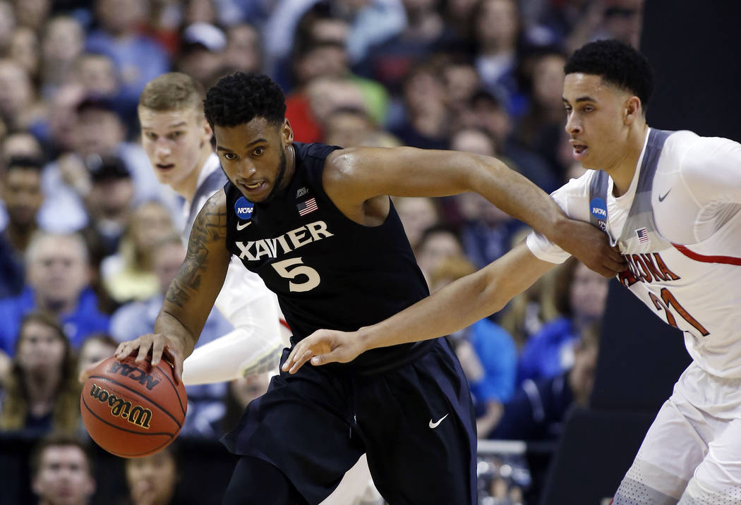 Xavier guard Trevon Bluiett (5) dribbles next to Arizona center Chance Comanche (21) during the first half of an NCAA Tournament college basketball regional semifinal game Thursday, March 23, 2017 ...