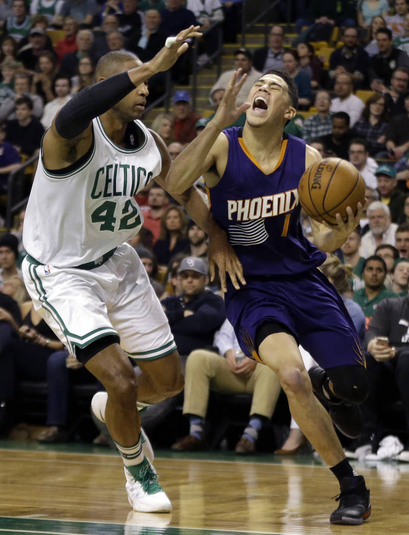 Phoenix Suns guard Devin Booker (1) drives against Boston Celtics center Al Horford (42) during the first quarter of an NBA basketball game, Friday, March 24, 2017, in Boston. (AP Photo/Elise Amen ...