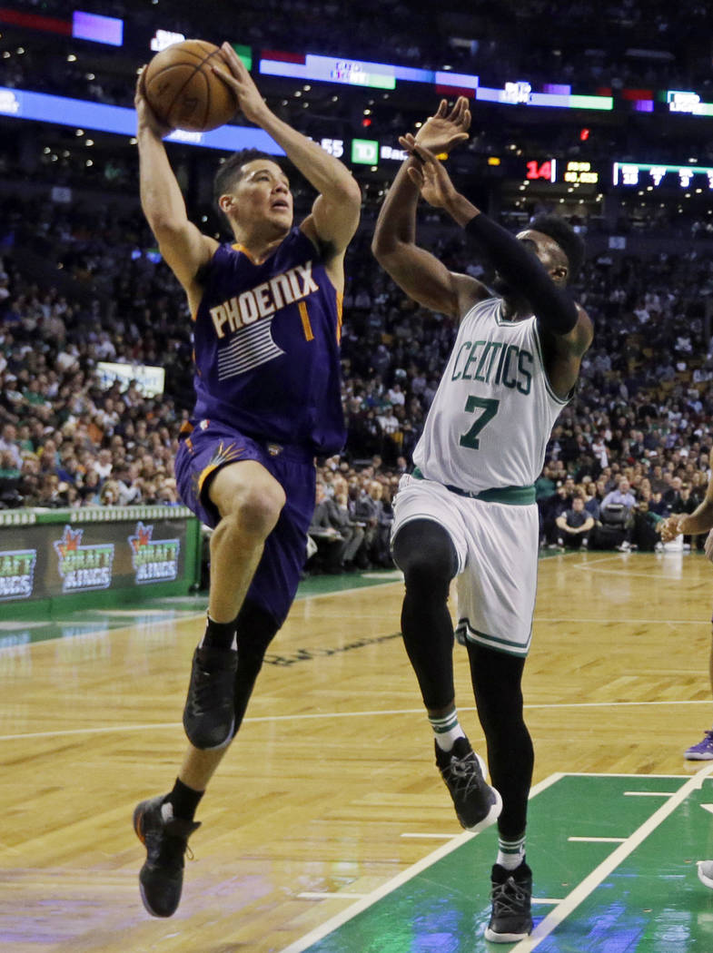 Phoenix Suns guard Devin Booker (1) goes up for a shot against Boston Celtics forward Jaylen Brown (7) during the first quarter of an NBA basketball game, Friday, March 24, 2017, in Boston. Booker ...