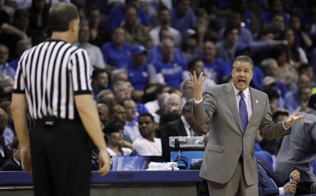 Kentucky head coach John Calipari speaks with an official in the first half of an NCAA college basketball tournament South Regional semifinal game against UCLA, Friday, March 24, 2017, in Memphis, ...