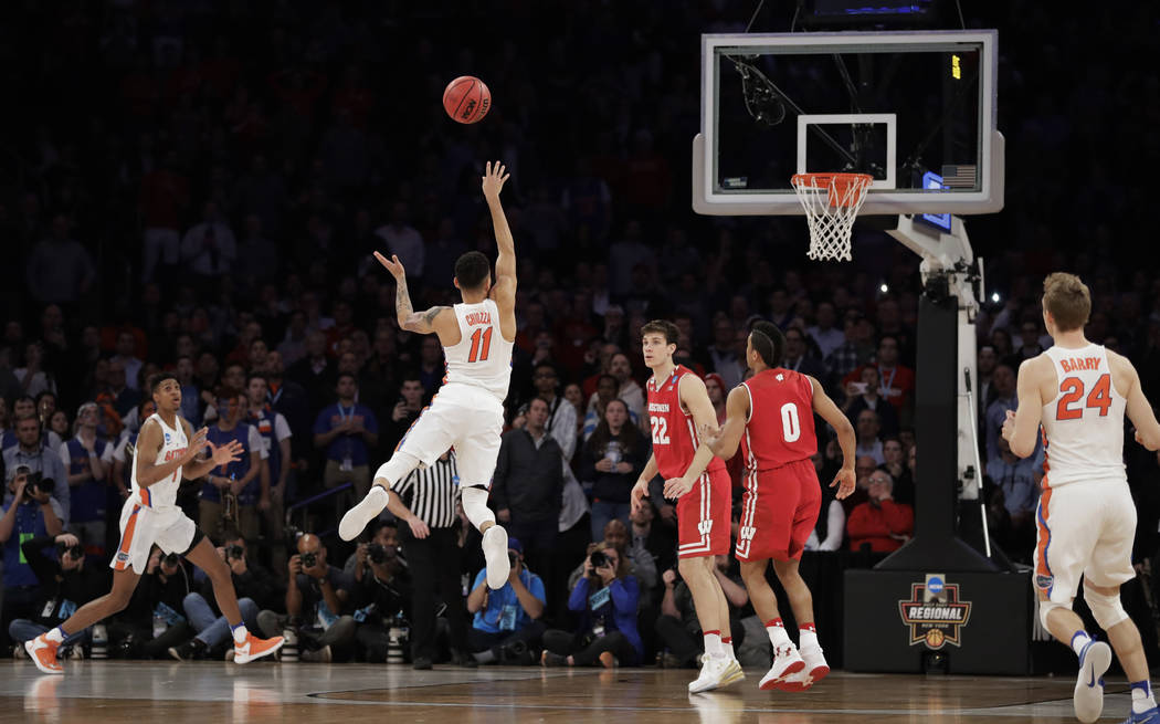 Florida guard Chris Chiozza (11) puts up a last second 3-point shot to score the game-winning points against Wisconsin in overtime of an East Regional semifinal game of the NCAA men's college bask ...
