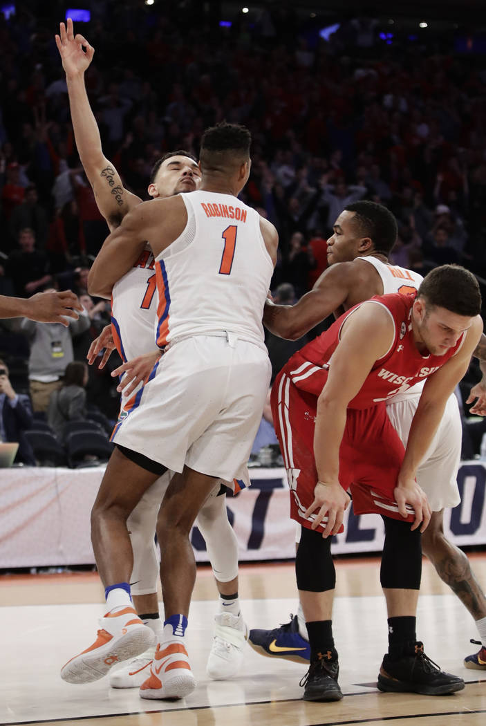 Florida forward Devin Robinson (1) hugs guard Chris Chiozza (11) after Chiozza hit the game winning shot in overtime against Wisconsin at an East Regional semifinal game of the NCAA men's college  ...
